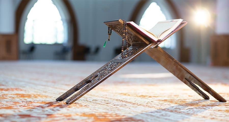 Coran ouvert posé sur un support en bois dans une mosquée