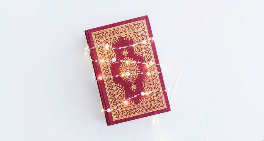 Coran fermé rouge entouré d'une guirlande lumineuse